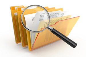Magnifying glass looking through folders
